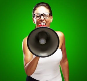 portrait of middle aged woman shouting with megaphone over grey background